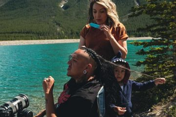 Drezus getting his hair braided by his wife with his son pulling a strand of his sitting by a lake