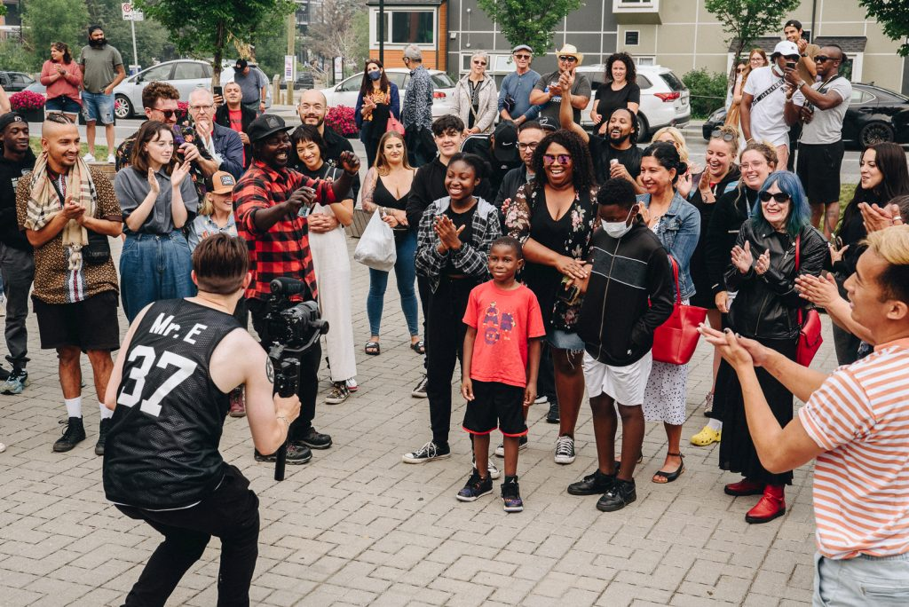 a group of people gathered together watching a young boy dance